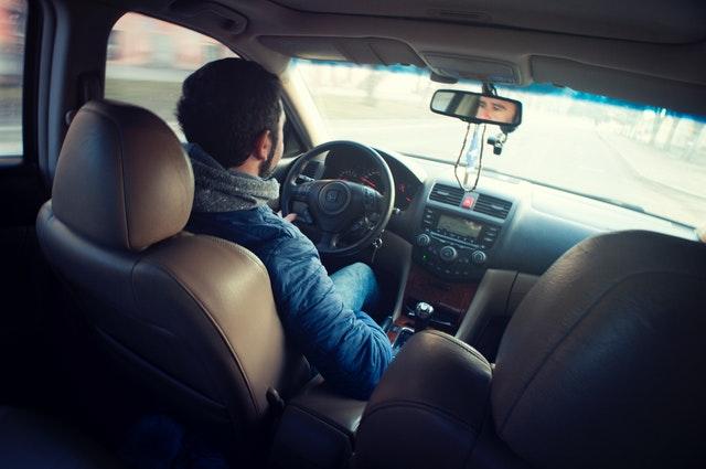 Muž sedí za volantom v aute a šoféruje.jpg