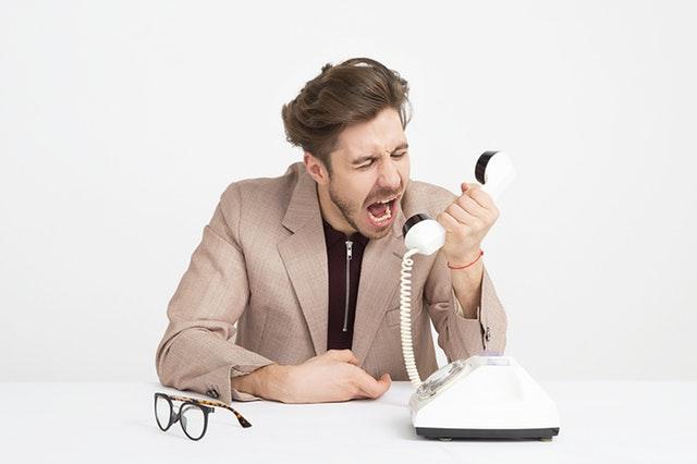 Muž v hnedom saku vrieska do telefónu.jpg